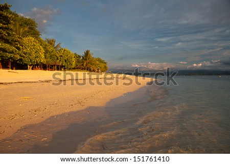 A white sand beach on Gangga Island, just north of the island of Sulawesi in Indonesia, is lit by the last light of day.  This region is known for its high marine biodiversity. #151761410