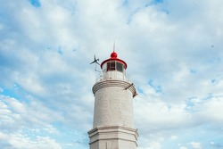 A white sea shore lighthouse with a red roof against a clear blue sky with white clouds on a Sunny day.