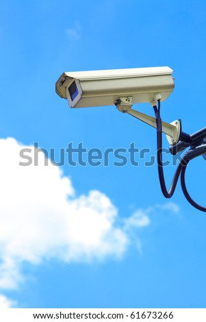 A white security camera and blue sky