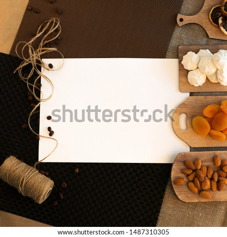 A white sheet of paper on the left is a twine rope and coffee grains, on the right there are pieces of dried orange with pieces of dried orange, dried apricots, marshmallows and almonds