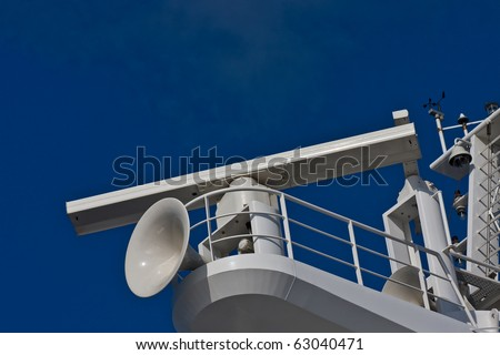 A white ships horn and radar on a tower of a cruise ship