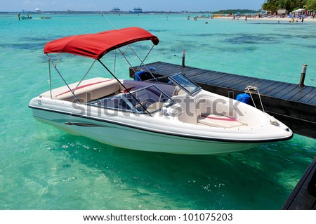 A white speedboat docked on a beach