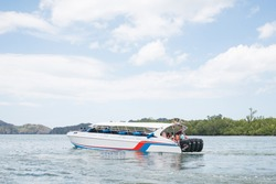 A White Speedboat vehicle of water has passenger or tourism take in the boat. Speedboat move on the sea or bay. Water travel or water transport concept. Comfortable travel.