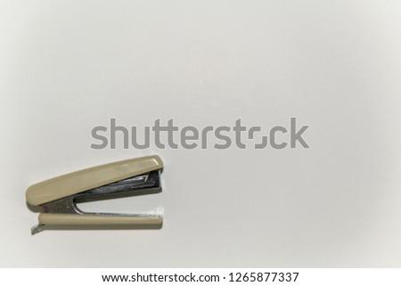 A white stapler at the lower left corner on white background