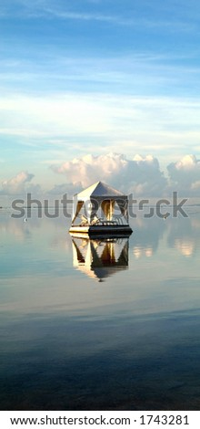 A white tent with lounge chairs floats in the waters off Sanur Beach, Bali. - stock photo