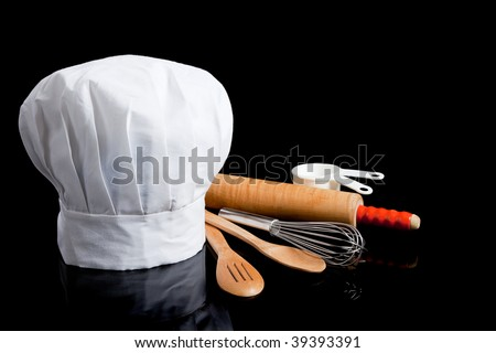 A white toque with cooking utensils including rolling pin, wooden spoons, whisk and measuring cups on a black background