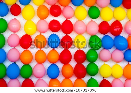 A white wall with colorful balloons attached. Photo is of a boardwalk arcade game where you throw darts and try to pop balloons. Only the wall of balloons is shown.