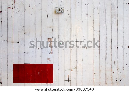 A white wall with vertical lines cracking in the paint and a red rectangle at the bottom left.  Ideal for a design layout of a simple sort with plenty of copy space and room for text.