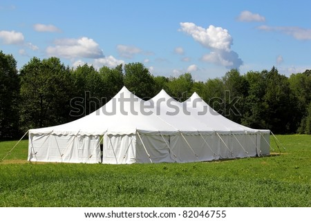 a white wedding or entertainment tent in a grass field on a sunny summer's day - stock photo