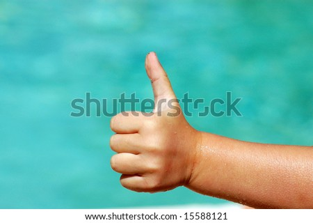 A white wet hand of a caucasian child showing the thumb up being very optimistic