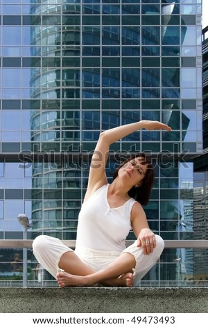 a white woman is exercising yoga and meditation in front of a modern office building.