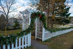 A white wooden archway and white wood picket fence surrounding a garden. There's a green Christmas garland hanging along the top of the fence and around the arch. The garden has trees and green grass.