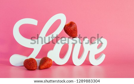 a white wooden sign saying LOVE with 1 strawberry leaning against the letters and two strawberries in front on a pink background