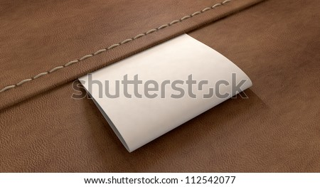 A white woven clothing label sewn into seamed brown leather