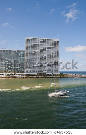 A white yacht motoring into a shipping channel past modern white condos