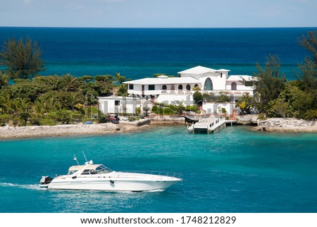 A white yacht passing by the residential house built on a narrow land of Paradise Island between Nassau Harbour and Caribbean Sea (Bahamas). Foto stock ©