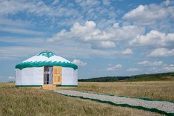A white yurt (the house of nomadic people, Bashkiria) stands in the steppe with an open door against a blue summer sky