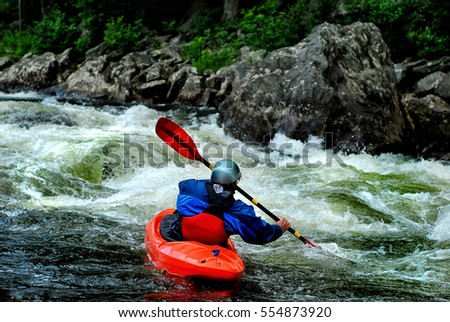 A whitewater kayaker braces in fast moving water on the river