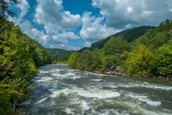 A whitewater raft and a few kayaks going down the fast current of the Ocoee river in Tennessee with the woodlands and fluffy cloud sky surrounds the whitewater on a bright day in late summer