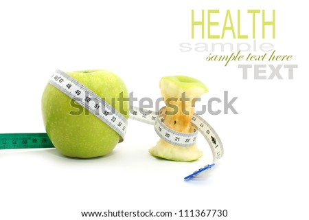 A whole green apple and a eaten green apple with measuring tape isolated on white