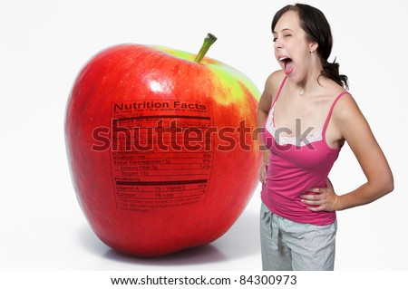 A whole red delicious apple with a nutrition label