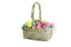 a wicker basket of colorful pastel Easter eggs isolated on white
