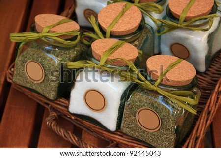 A wicker basket with jars containing salt and spices, closed with cork plugs and green ribbons