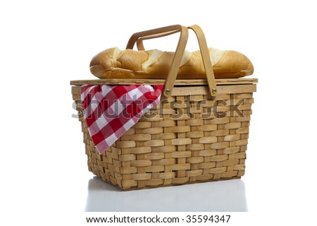 A wicker picnic basket with a red gingham cloth and bread on a white background