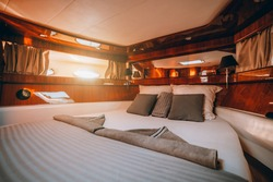 A wide-angle fragment of a interior of a luxurious boat cabin with a big neatly made bed, lacquered wood paneling decoration, stripe of mirrors and an area with portholes with a sunny day outside