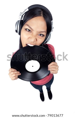 A wide angle full body shot of a female Asian DJ biting a record and wearing headphones
