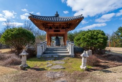 A wide angle photo of a traditional Korean pavillion in the Bell Garden of the Meadowlark Botanical Gardens in Vienna, Virginia.