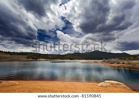 A wide angle shot of a lake in front of the Rocky Mountains.