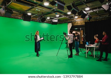 Photo of  A wide-angle shot of a multi-ethnic group of people working in a film studio, a mature caucasian woman can be seen presenting in front of a green screen.