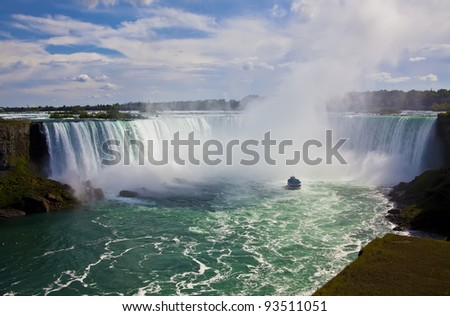 A wide angle shot of the Horseshoe Falls in Niagara. A tour boat is positioned at the base. #93511051