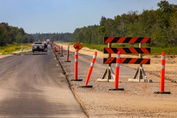 A wide angle view of a new freeway construction through a natural lush green forest landscape, tree lined on both side with roadwork signs and cones