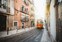 A wide-angle view of a red retro tram on a narrow street with one-way rail traffic in a European city; a vintage tourist streetcar in red and yellow colors on a tramway track over paving stone, Lisbon