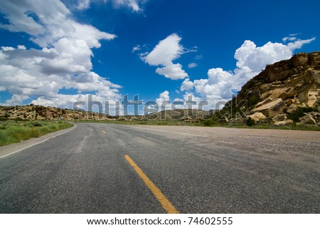 A wide angle view of an American highway stretching through a rocky countryside