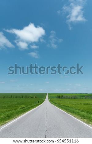A wide asphalt road between green fields