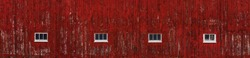 A wide barn side red painted wall that is aged and textured with 4 windows.