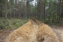 A wide barrage ditch in sandy soil against a fire in a pine forest near St. Petersburg. Environment protection.