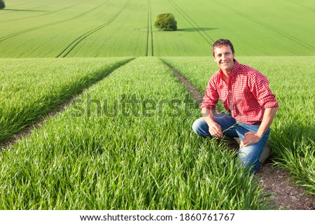 A wide horizonal portrait of a smiling farmer crouched down in a wheat field while holding a crop in his hand Сток-фото ©