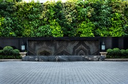 A wide neatly paved stone courtyard  with backdrop of various leaf walls.