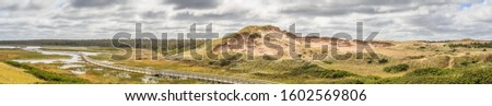 A wide panorama photo of grassy sand dunes the size of mountains in bright sunshine under storm clouds on the beautiful Atlantic coast of Prince Edward Island, Canada.