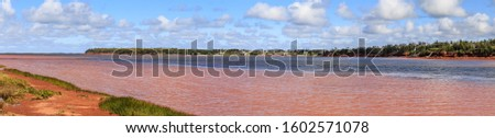 A wide panorama view of the scenic coast and unique red muddy coastal waters of Prince Edward Island after a powerful hurricane.