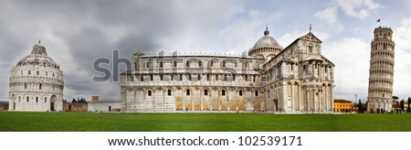 A wide panoramic photograph of Piazza dei Miracoli containing the Leaning Tower of Pisa, the Cathedral and Duomo taken with a very long exposure to create motion blur on the tourists. - stock photo