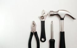 A wide range of household tools on a white background: screwdriver, adjustable wrench, pliers and hammer. Top View.
