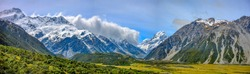 A wide screen view of the mountains at the top of the mountain is snow in the summer with sky and green grass in Mount Cook National Park in the southern island of New Zealand.