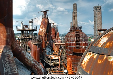 A wide shot of a decaying rusting steel plant with several furnaces and blast chambers.
