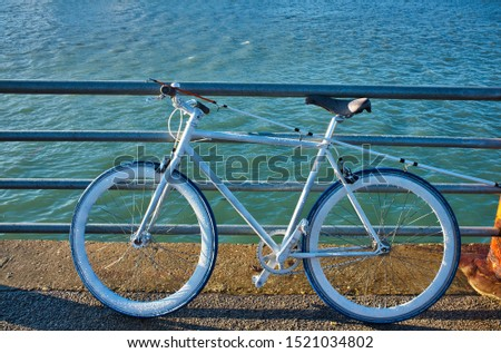 A wide shot of a road bicycle parked near the water during daytime in Dunkerke, France #1521034802