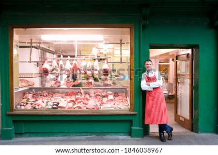 A wide shot of a young smiling butcher in red apron leaning against butcher shop doorway next to the display window. Foto stock ©